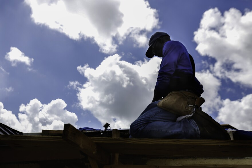 Pastor Cecil Kemp looks at his tools while starting repairs on the roof of his home in High Rock, Grand Bahama on September 16, 2019. On the road where Kemp lives, Solomon Drive, only four houses remain occupied and 17 people from the community died in th