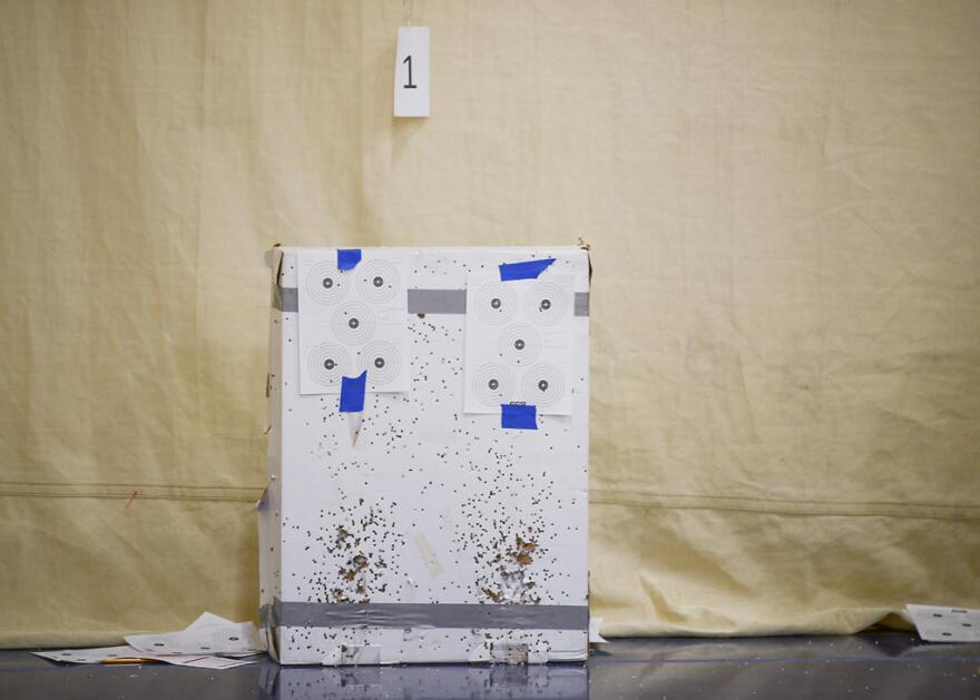 A set of targets sit on cardboard filled with holes from air rifles between rounds at a Student Air Rifle Program tournament in the gym of Clever High School in Clever, Missouri on Nov. 14, 2019. The SAR program is funded in part by the NRA Foundation.