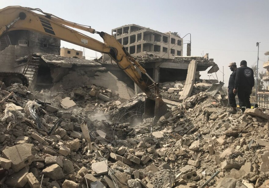 Raqqa's first responders use a digger to push through the rubble of a building likely destroyed in an airstrike carried out by the U.S.-led coalition against ISIS.