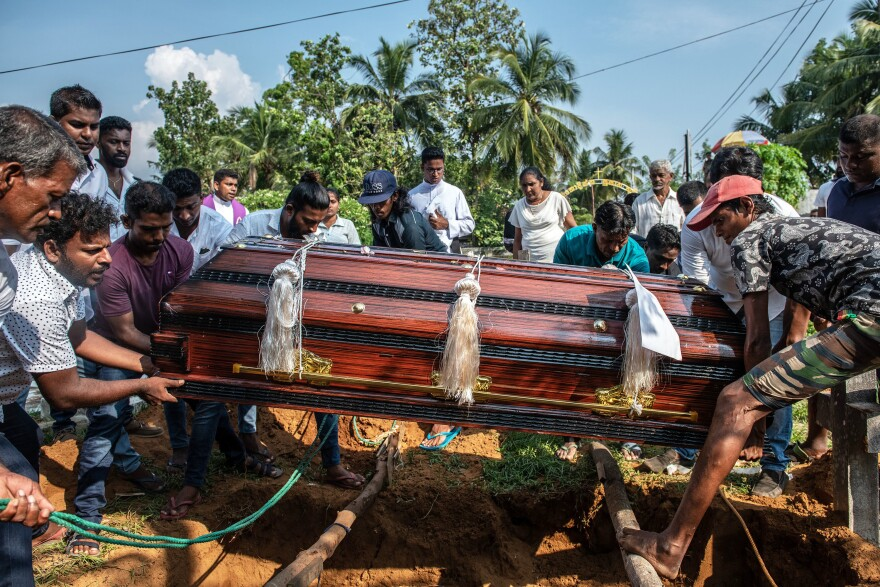 A coffin is lowered into a grave during the funeral of a person killed in the Easter Sunday attack on St. Sebastian's Church in Sri Lanka.