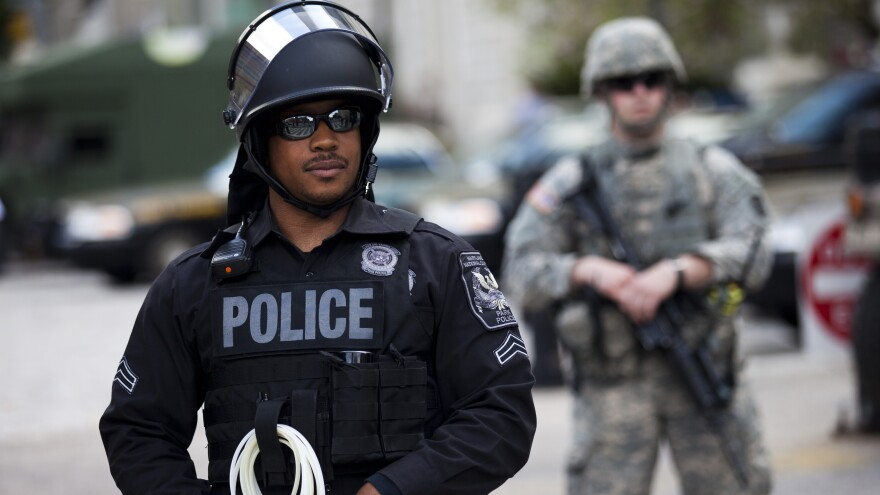 A National Guardsman and a police officer hold their positions at City Hall during a protest Wednesday in downtown Baltimore. Thousands marched, demanding justice for an African-American man who died of severe spinal injuries allegedly sustained in police custody, but most were off the streets shortly after the 10 p.m. curfew.