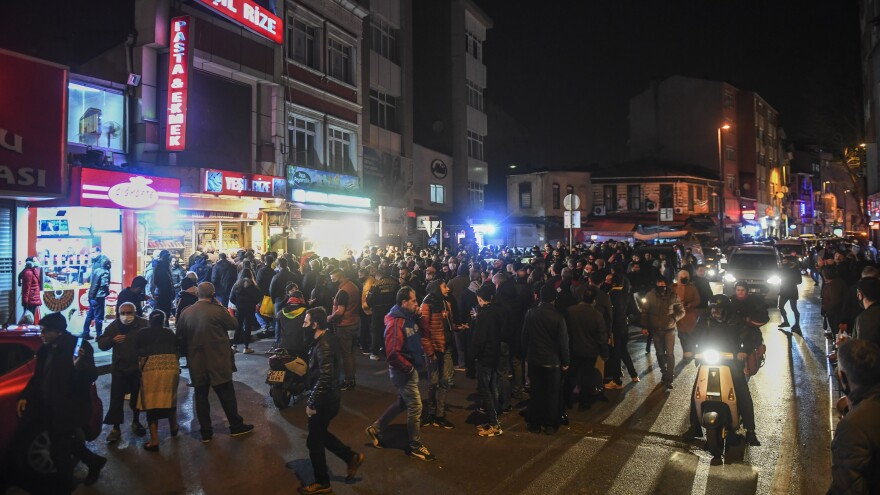 People crowd a convenience store in central Istanbul to buy last-minute groceries, after Turkish authorities announced a weekend curfew just hours before it took effect overnight Friday.