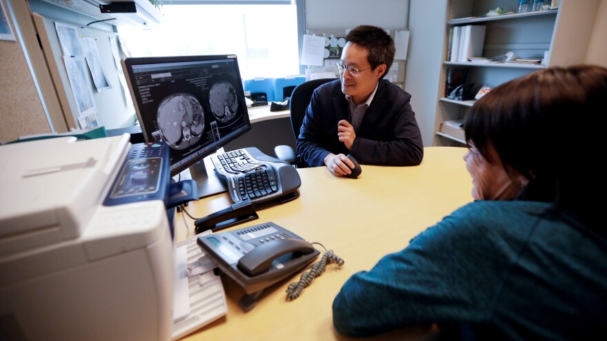 A patient looks at images with her doctor in this file photo.