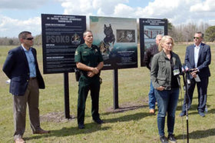 USF forensic anthropologist Erin Kimmerle speaks at the institute's proposed site on the Pasco Sheriff's Office property in Land O'Lakes Monday, while (from L-R) Rep. Danny Burgess, Sheriff Chris Nocco and County Commissioners Ron Oakley (obscured) & Mike Moore look on.