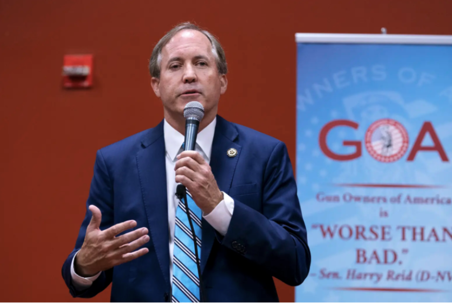 Texas Attorney General Ken Paxton stands speaking into a microphone. He is dressed in a suit and holding the microphone.
