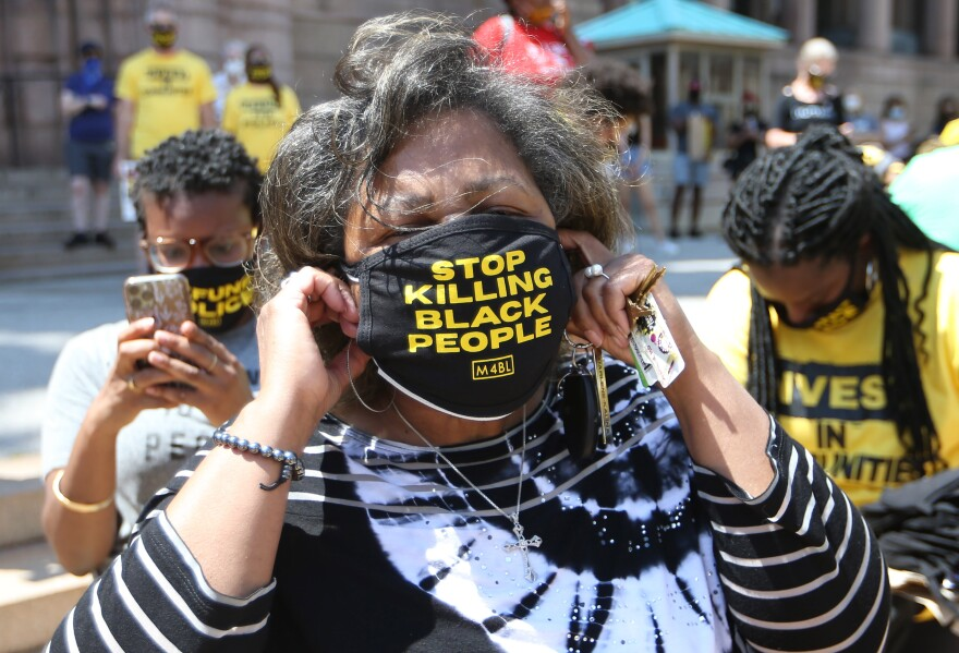 St. Louis Comptroller Darlene Green puts on a mask during a Juneteenth celebration at St. Louis City Hall in St. Louis on Friday, June 19, 2020.