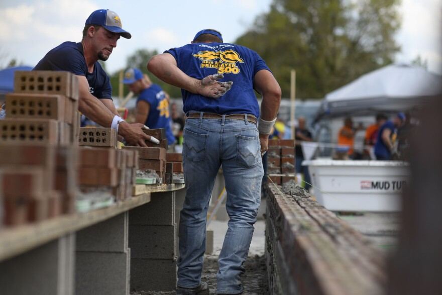 Jake Payne, left, stacks a pile of bricks while J.T. Payne rushes to build their 26-foot-long wall during the Spec Mix Bricklayer 500 competition in Bridgeton, Mo on September 12, 2019.