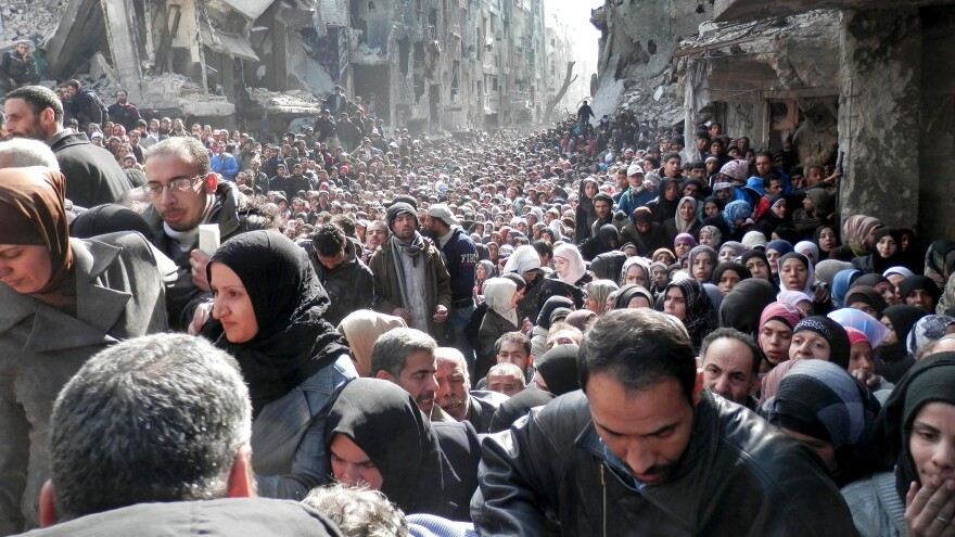 This January 2014 shows thousands of residents of Yarmouk, a Palestinian neighborhood of Damascus, lining up for food. The photo went viral and drew attention to civilians at risk in Syria, but the fighting has continued unabated.