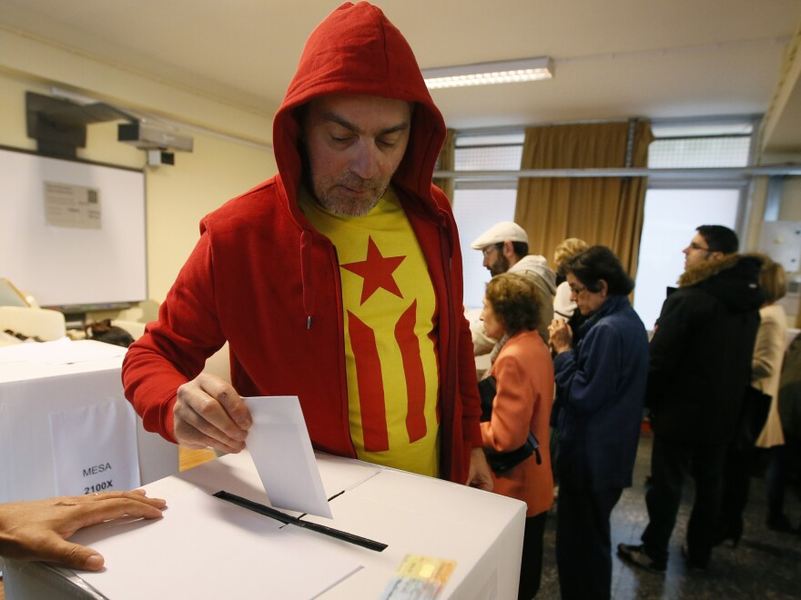 A man wearing a Catalan Nationalist flag T-shirt casts his ballot in a symbolic independence vote in Barcelona on Sunday.