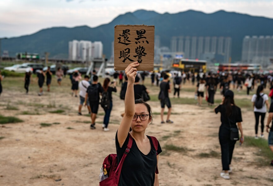 """A protester holds up a placard that roughly translates to """"Policeman, give the eye back."""""""