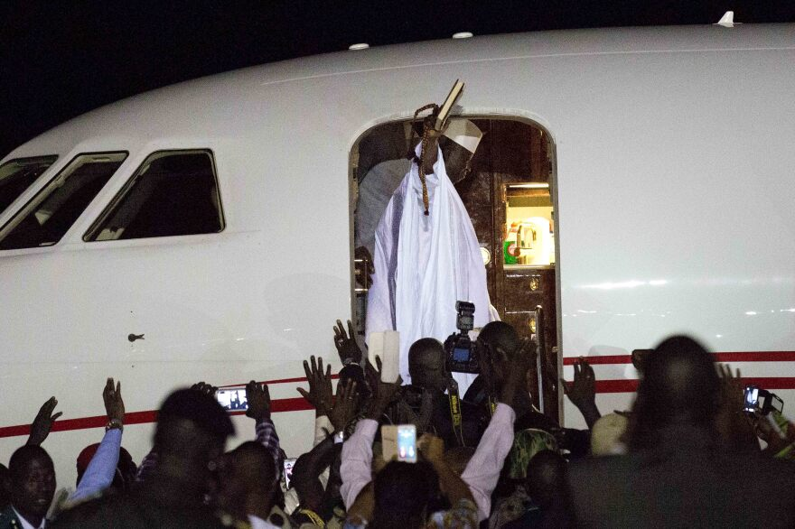 Gambia's defeated leader Yahya Jammeh waves to supporters as he departs from Banjul airport on Saturday.