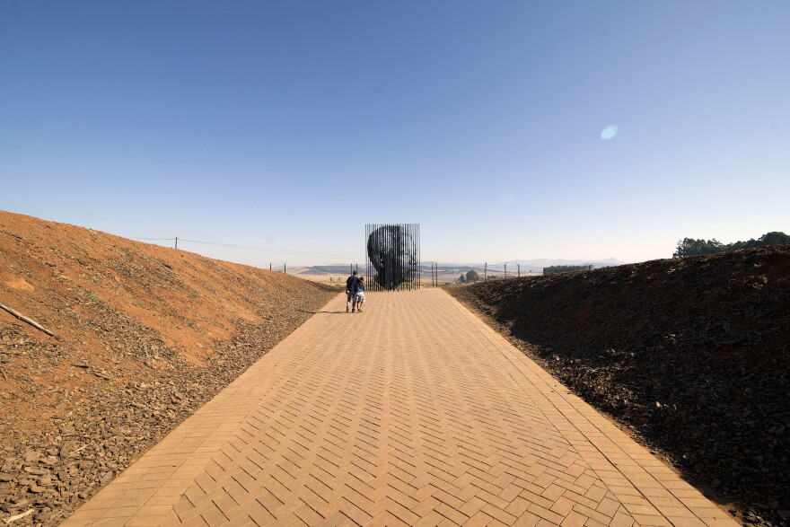 As visitors walk up a pathway, the steel columns align to reveal the face of Nelson Mandela.