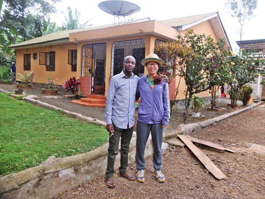 Godwin Ndosi rents out rooms at his parents' house to guests around the world through websites like Airbnb. He's standing with one of his international visitors.