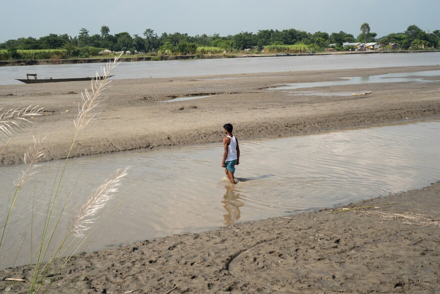 A young man living on a small river island known as a char heads out to catch a boat and cross the Brahmaputra River to the mainland, in Assam's Barpeta district. To live in Assam legally, people must be registered by the government. But some 4 million people have been excluded from the National Register of Citizens, a sort of statewide census.