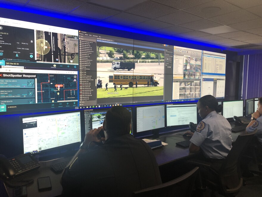 Members of the Miami-Dade County Public Schools police force monitor a simulated emergency on a school bus from the department's command center. A dozen screens cover the wall, showing live feeds from school surveillance cameras.