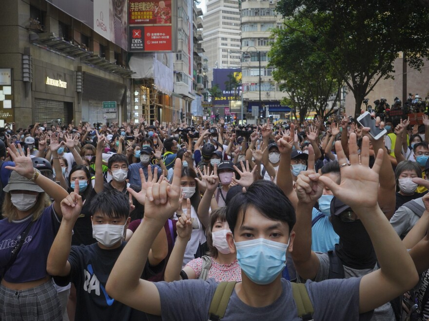 """Protesters against the new national security law gesture with five fingers, signifying """"five demands — not one less"""" on the anniversary of Hong Kong's handover to China from Britain in Hong Kong on Wednesday."""