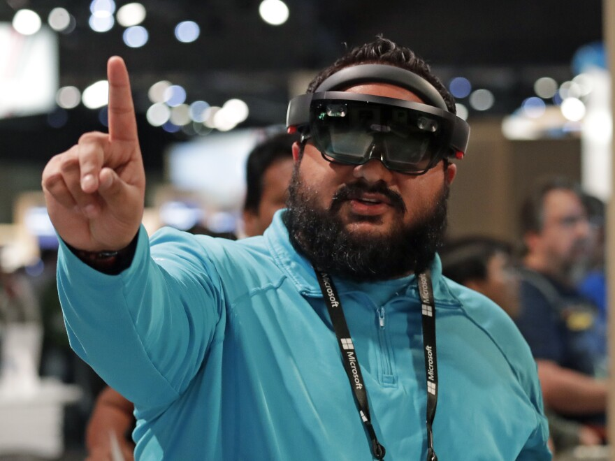 Raman Ghuman demonstrates a HoloLens device at Microsoft's annual conference for software developers on May 7, 2018, in Seattle. Microsoft workers are protesting the use of the augmented reality technology in a U.S. Army contract.