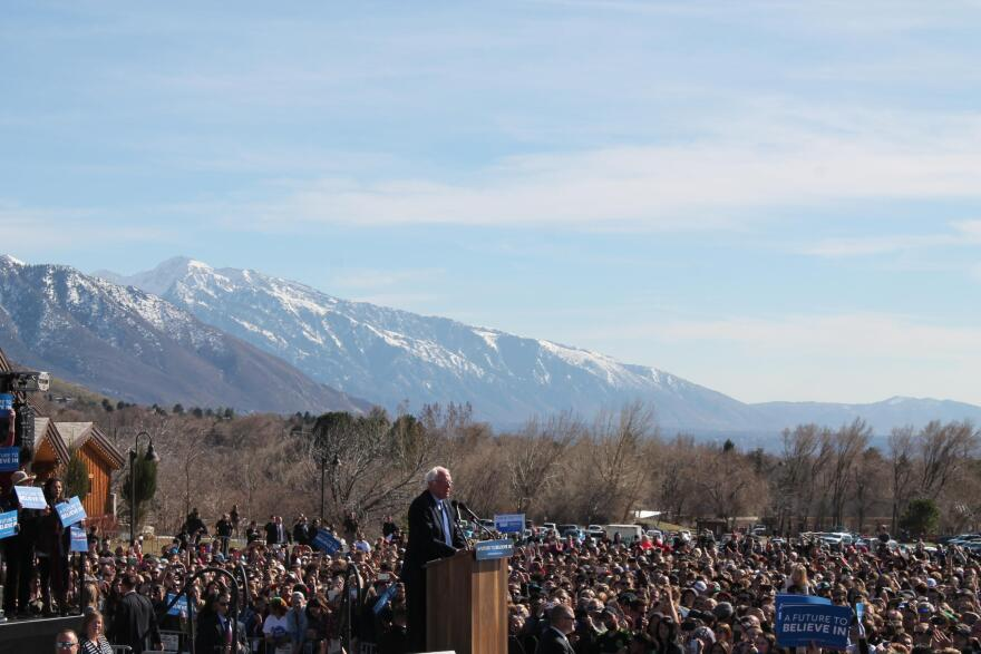 Bernie Sanders standing at a podium on a stage surrounded by thousands of people.