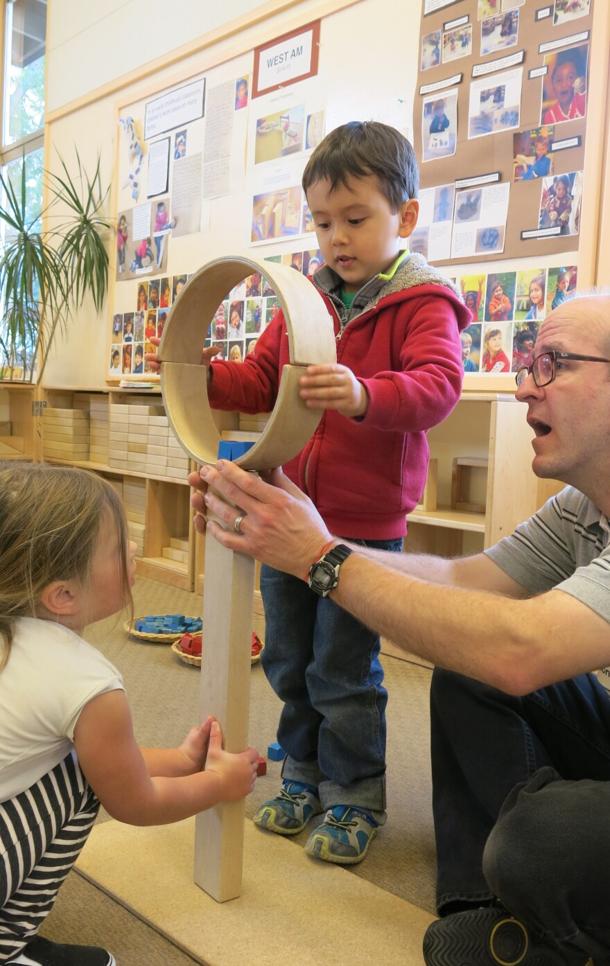 Four-year-olds Jacques and Corinne work with teacher Todd Erickson to balance and secure two semicircular wooden blocks atop two long, straight ones.