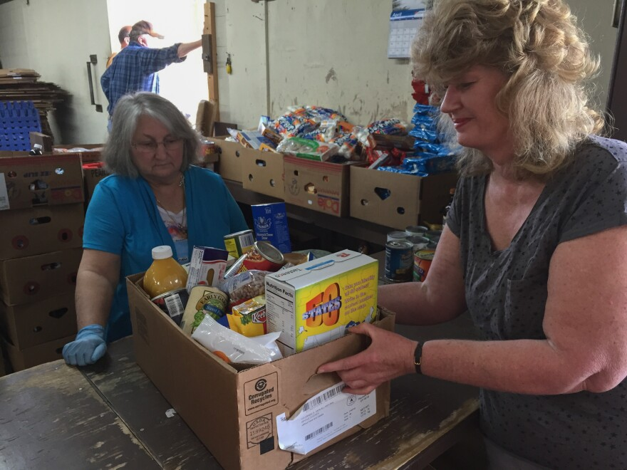 Cathy Rose is getting a box of free food from volunteer Rilda White at the pantry in Clintwood, Va. Rose says she relies on the free food because she lives on Social Security disability and the monthly check doesn't cover her bills.