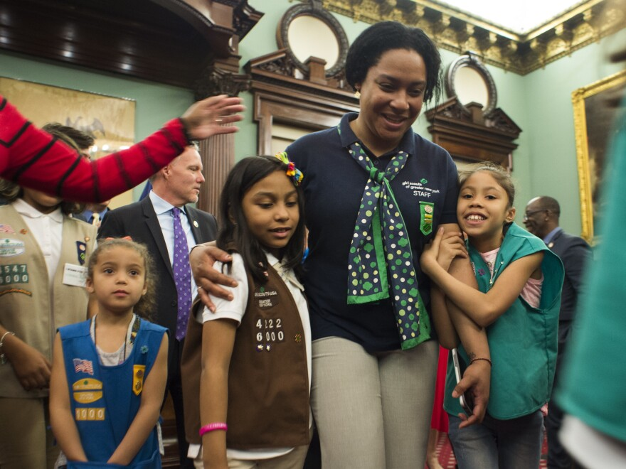 Members of Girl Scout Troop 6000 troop and leader Giselle Burgess hug after being honored as the first troop exclusively for homeless girls, at a ceremony at New York City Hall on April 25.