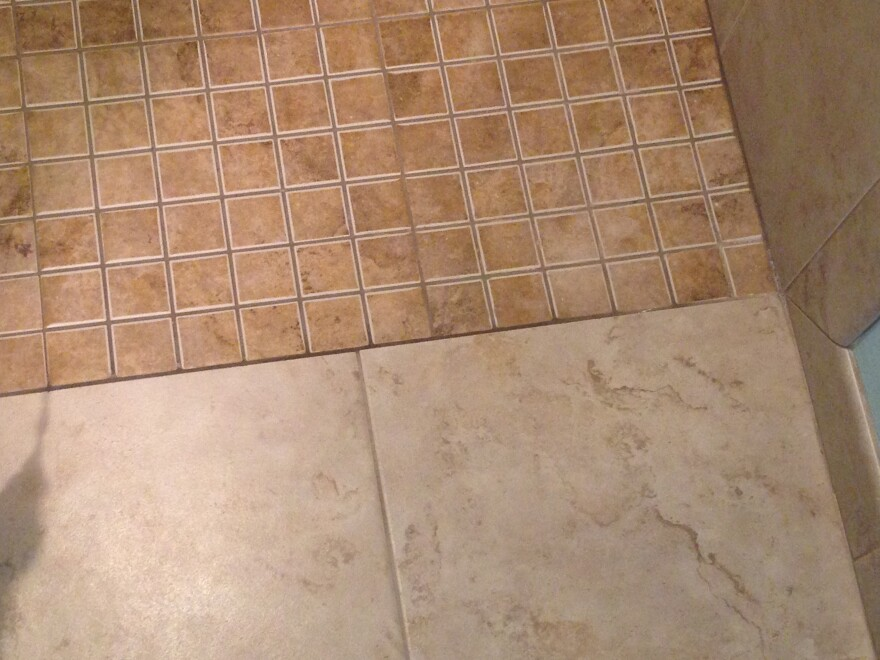 The bathroom has a barrier-free shower. Here is the transition from the regular bathroom tile to the shower tile.