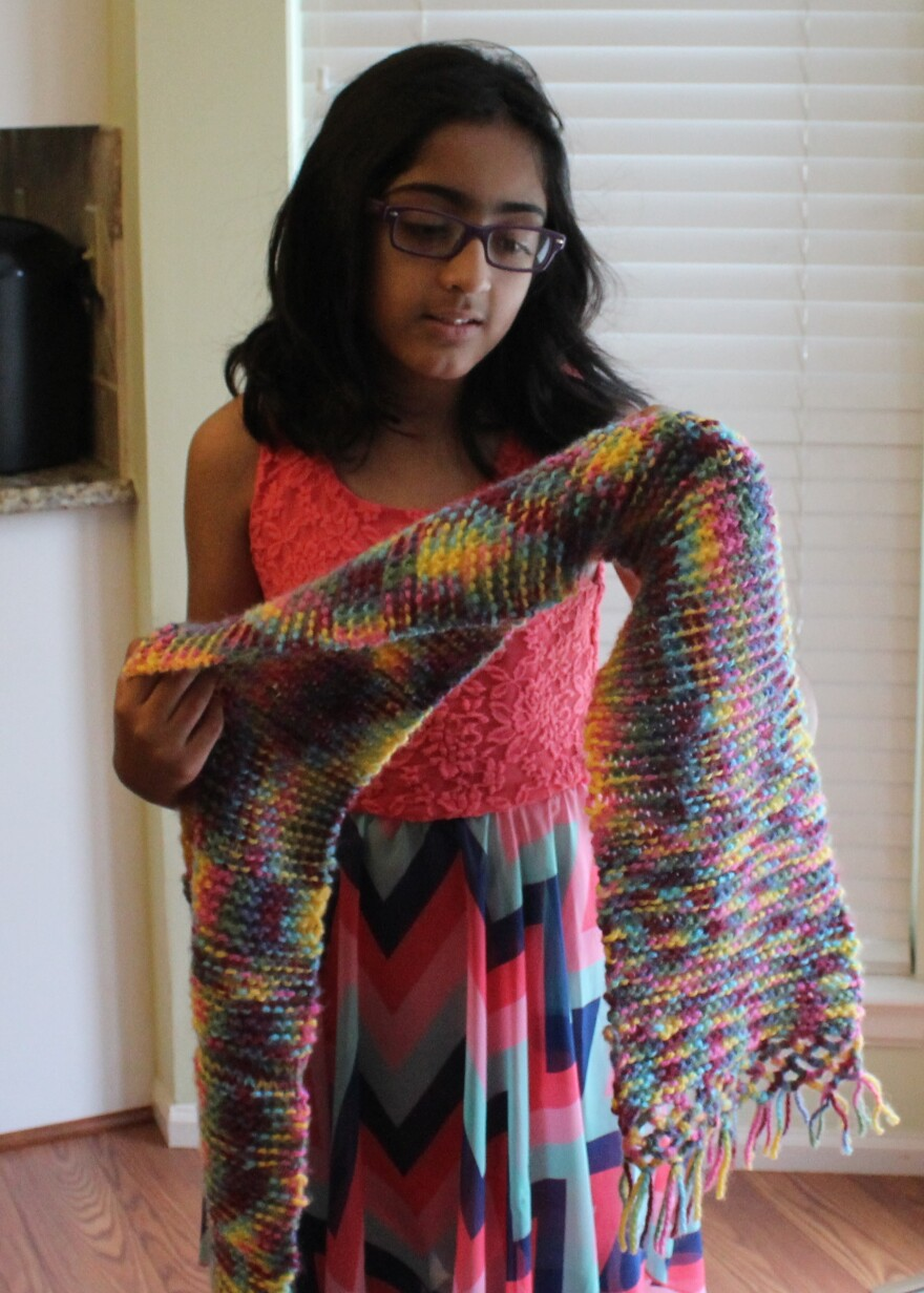 Tanya Raja, 11, shows off a scarf she knit, in part, while she was fasting during Ramadan.