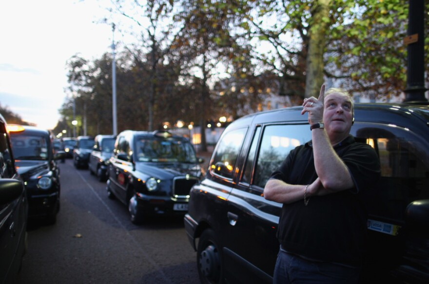 A taxi driver stands outside his cab in London, England.