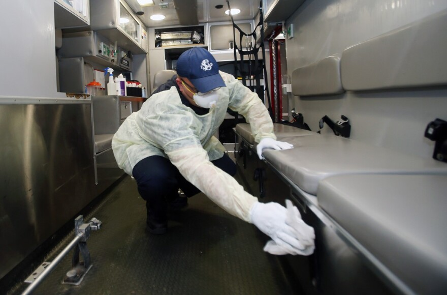 St. Louis Fire Department paramedic Andrew Beasley wears a mask, gloves and a gown as he disinfects the back of an ambulance with a bleach mix, after delivering a patient to Barnes-Jewish Hospital on March 16, 2020.