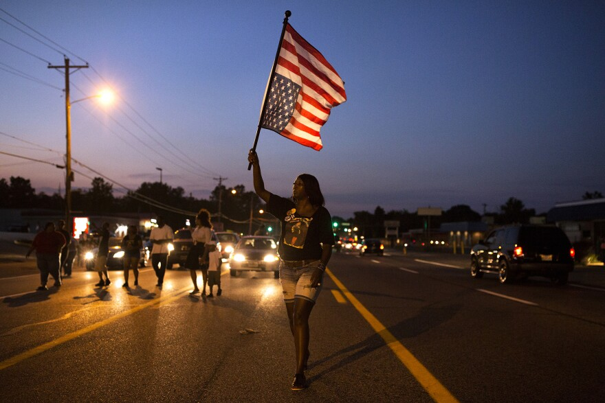 Demonstrators walk down West Florissant Avenue in Ferguson on Aug. 9, 2016, two years after Michael Brown was killed by a Ferguson police officer on nearby Canfield Drive.
