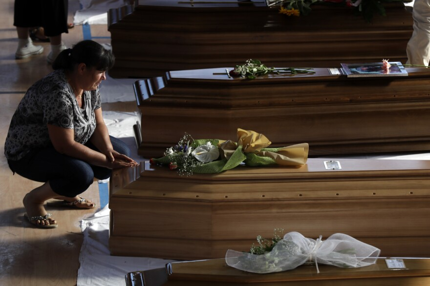 A woman touches a coffin of one of the victims of Wednesday's earthquake inside a gymnasium in Ascoli Piceno.