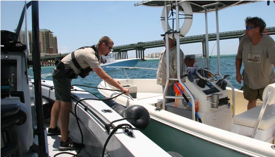Two boater pull alongside a Florida Fish and Wildlife boat for a check of their safety preparations