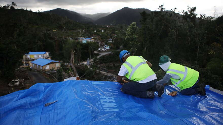 Contractors apply a FEMA tarp to a home in Morovis on Dec. 20, 2017, three months after it was damaged by Hurricane Maria. The day Maria hit, FEMA had fewer than 12,000 tarps on the island, far below what was needed.