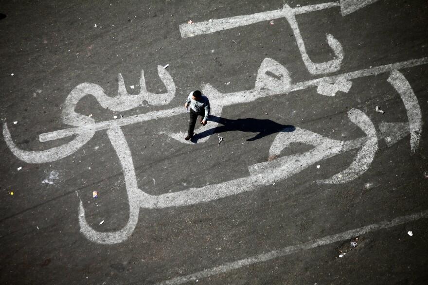 """An Egyptian man walks over a graffiti reading """"Morsi Go"""" at Egypt's landmark Tahrir square in Cairo."""