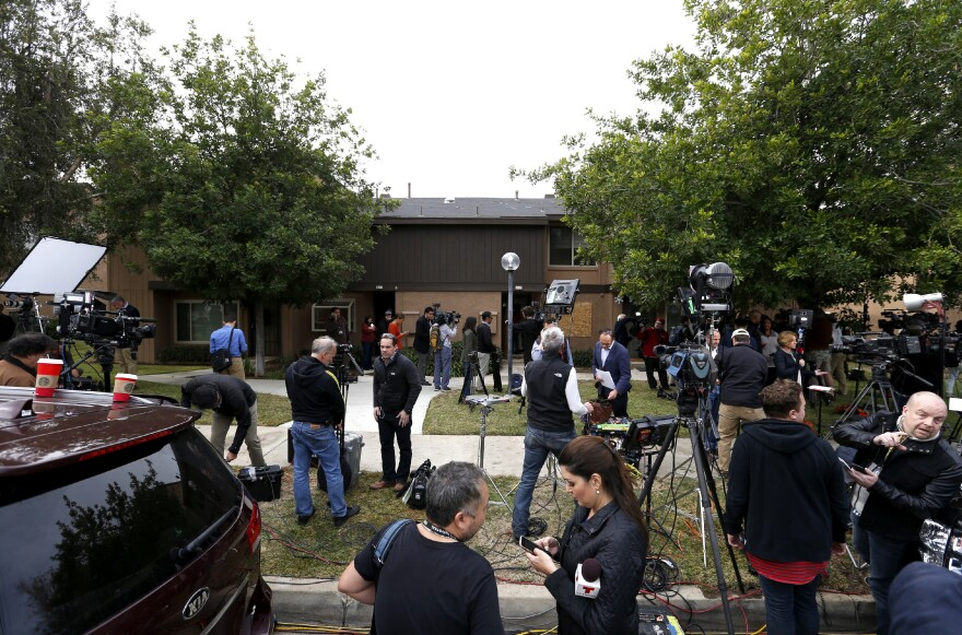 News media stand outside the home of San Bernardino shooters Syed Farook and Tashfeen Malik in Redlands, Calif., on Friday.