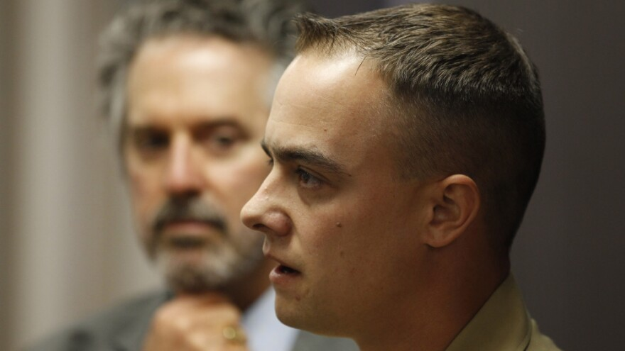 Marine Staff Sgt. Frank Wuterich talks to the media as his attorney, Neal Puckett, looks on after a 2010 pretrial hearing at Camp Pendleton in California. Wuterich is charged with voluntary manslaughter in the deaths of 24 Iraqi civilians in 2005.