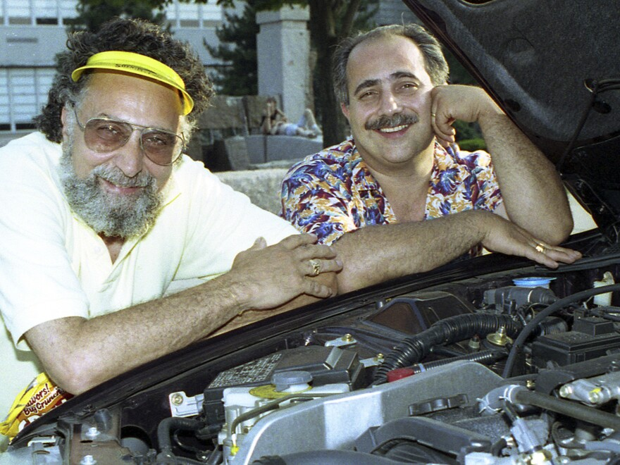 Brothers Tom (left) and Ray Magliozzi pose under a car hood in Boston. The comic duo hosted NPR's <em>Car Talk</em> for a quarter of a century before retiring in 2012. Since then, the show has been heard in reruns. Tom has died at age 77.
