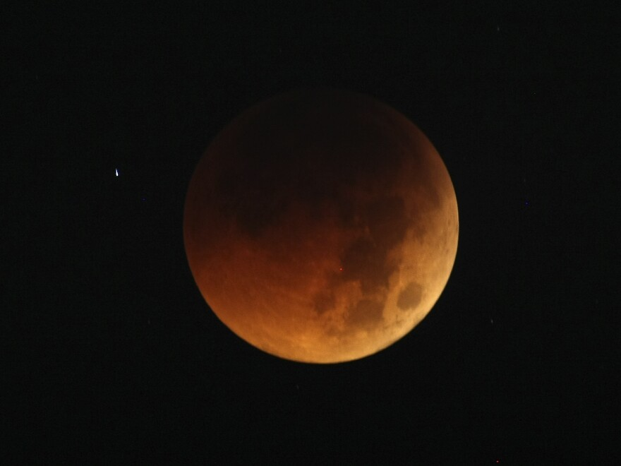 The moon exhibits a deep orange glow as the Earth casts its shadow in a total lunar eclipse as seen in Manila, Philippines, before dawn Thursday in a June 2011 eclipse.