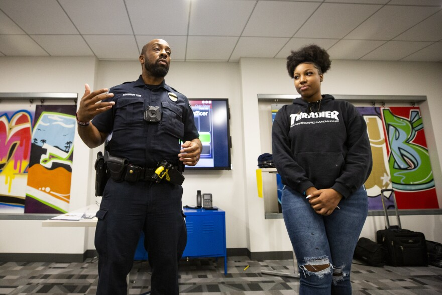 Austin Police Department Officer Jeremy Bohannon leads a portion of the Juvenile Justice Jeopardy workshop with student participant Cierra Moreland.