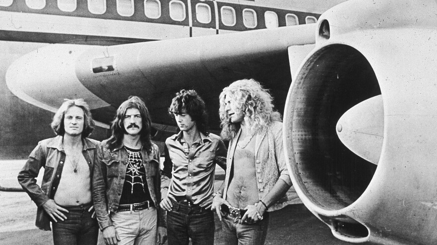 """British rockers Led Zeppelin pose in front of their private plane, dubbed """"The Starship,"""" in 1973."""