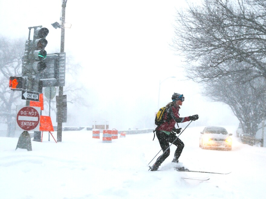 A woman cross country skis on snow-covered roads during a winter blizzard in Boston, Mass. Tuesday.