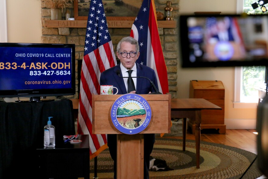 Gov. DeWine stands at a podium in his home for a coronavirus briefing.