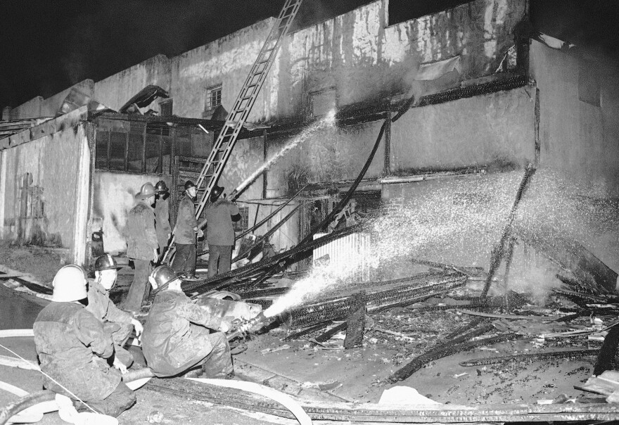 Firemen spray a stream of water on the burned-out grocery store in Augusta, Ga., May 12, 1970.
