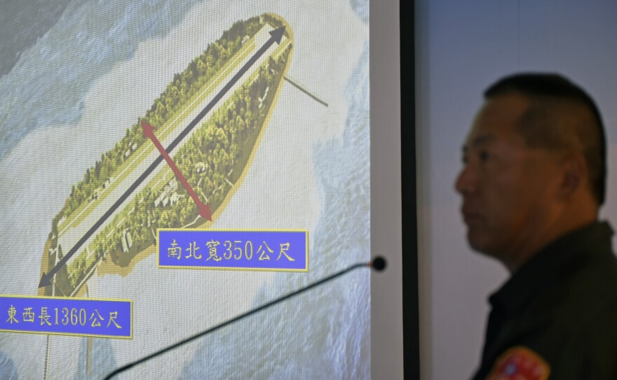 Wang Mao-lin, Taiwan's coast guard commander for the Spratly Islands, speaks next to an image of Taiping Island during a visit by journalists to the island on March 23. The island, claimed by Taiwan, is one of many that are dispute in the South China Sea.