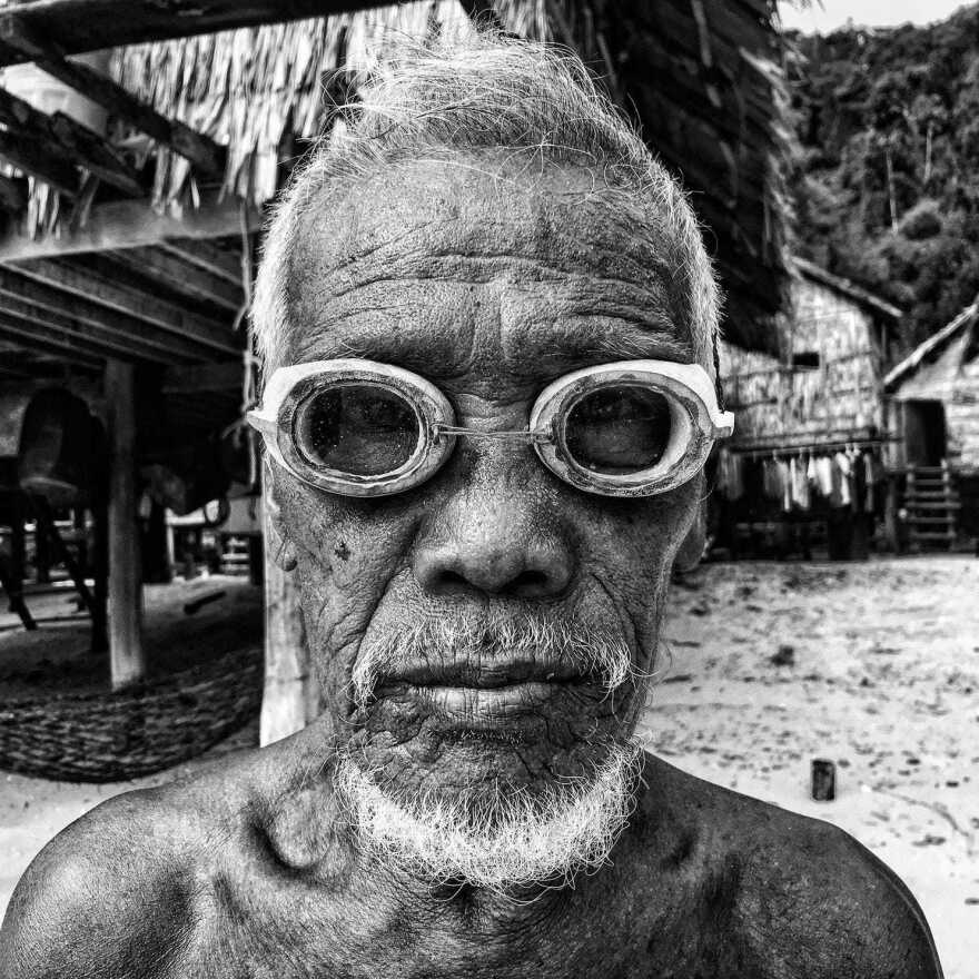 Village elder Salamah wears his hand-carved wooden dive goggles on the beach at Au Bon Yai, a tiny island community off the coast of Thailand.