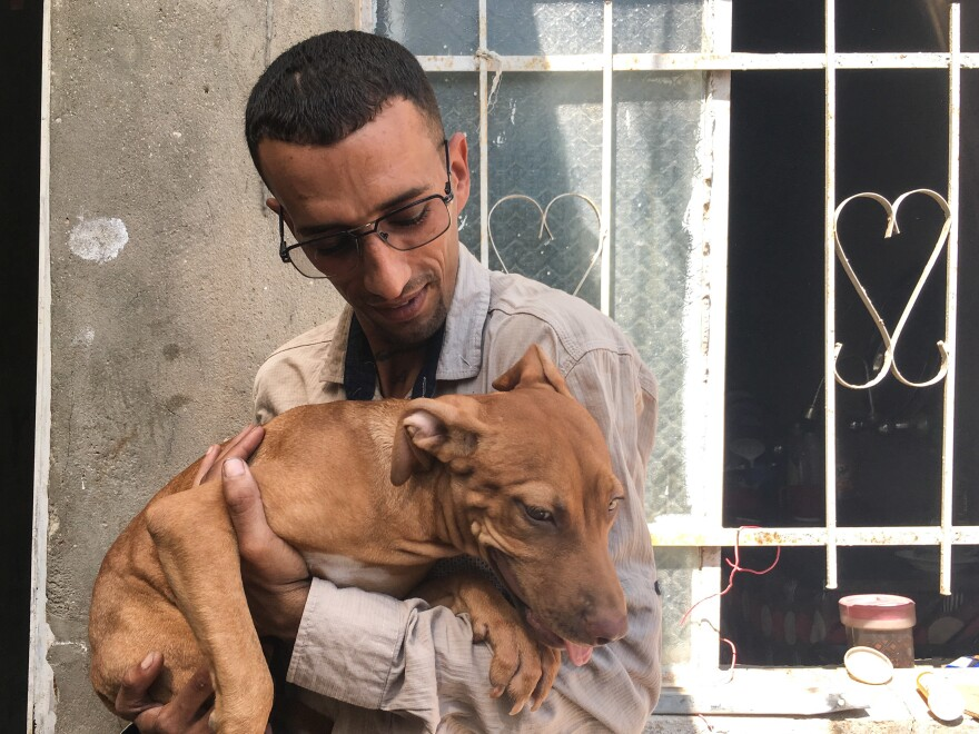 "Naser al-Shimary cuddles his dog. ""She is all the friends and family I have here,"" he says. Shimary says people in his neighborhood tell him dogs are religiously unclean. He is afraid she will be poisoned."