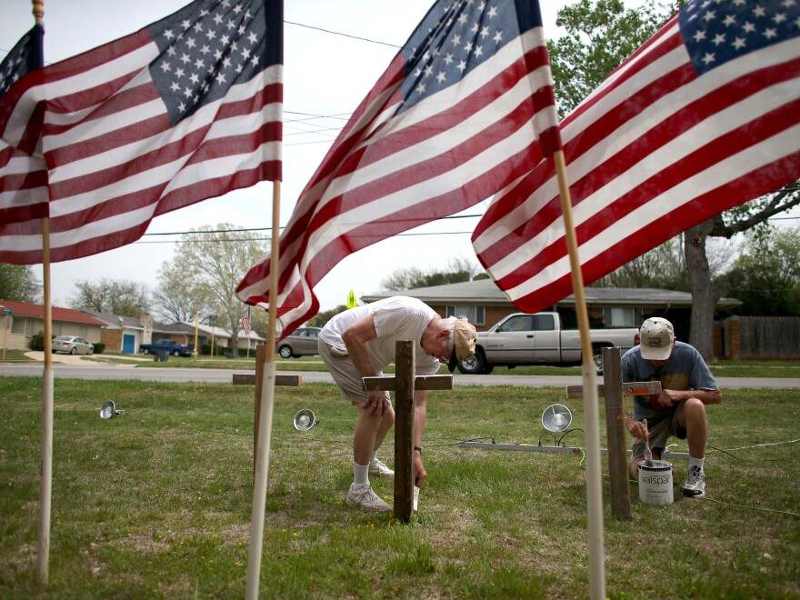 Bob Butler (left) and Bob Gordon paint crosses they placed in front of American flags at Central Christian Disciples of Christ church in the city of Killeen, Texas, which is home to Fort Hood.