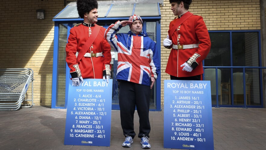 Royal supporter John Loughrey salutes as men dressed as soldiers carry boards with proposed baby names Friday outside the Lindo Wing of St. Mary's Hospital in London.