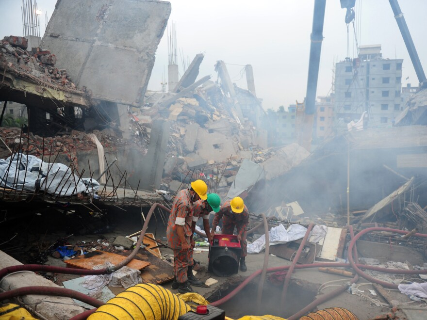 On April 29, 2013, Bangladeshi firefighters try to control a blaze during a rescue attempt as Bangladeshi army personnel begin the second phase of the rescue operation following the Rana Plaza collapse.