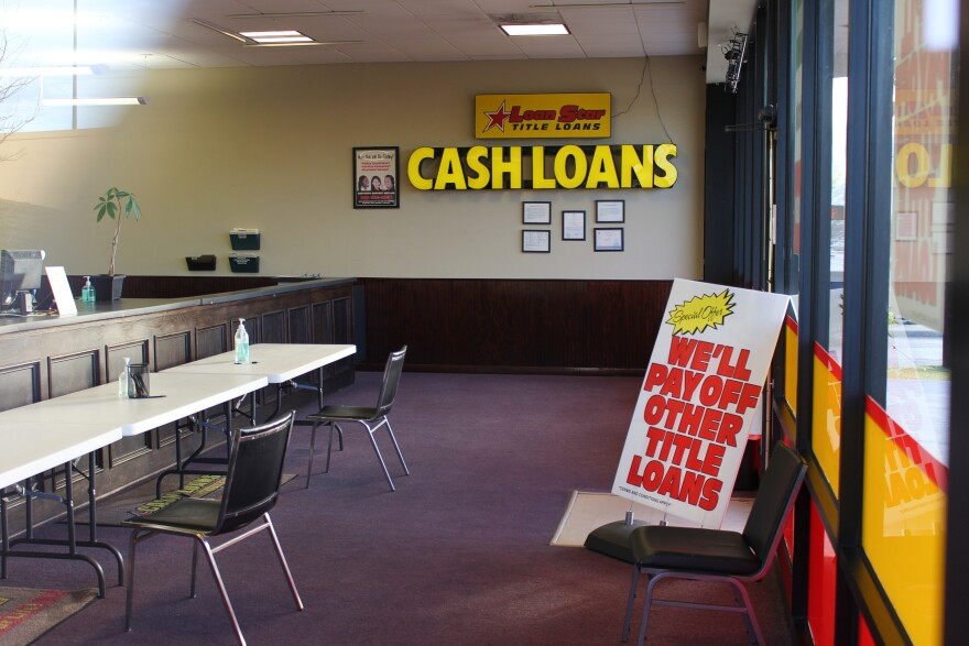 "Big yellow letters mounted to the wall inside this LoanStar Title Loans storefront say ""cash loans"" and a sign propped against the doorway reads, in bright red letters, ""We'll pay off other title loans."""